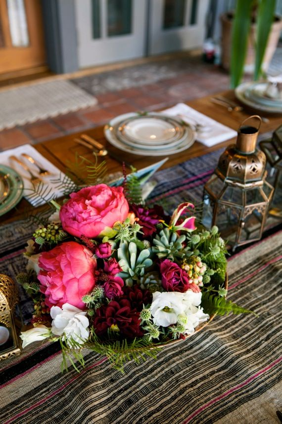 a folksy table runner, a bright floral centerpiece, Moroccan lanterns, printed plates