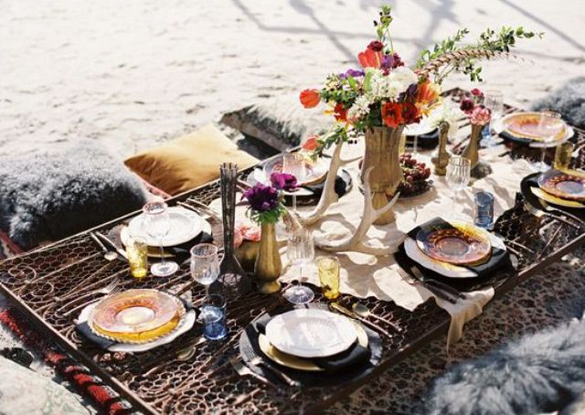 a picnic boho chic tablescape with a faux animal skin, antlers, bright florals and colored glasses and plates