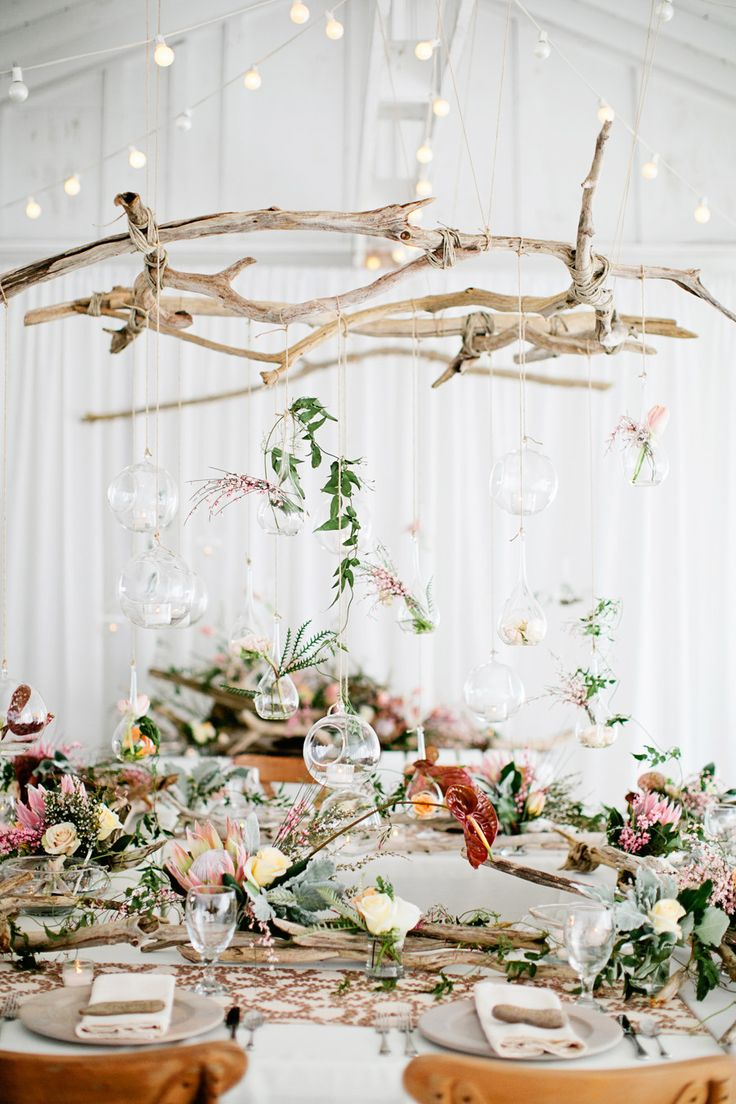 a boho tablescape with with floral decor, driftwood over the table and glass bubbles with blooms