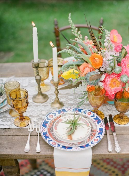 a lace table runner, colorful printed plates, colored glasses and super bright florals