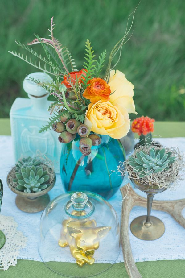 a turquoise vase with bright blooms, succulents, greenery and antlers for a woodland boho wedding