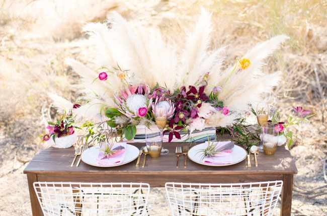 a lush and bright boho wedding centerpiece with dark blooms, greenery and pampas grass for a boho wedding
