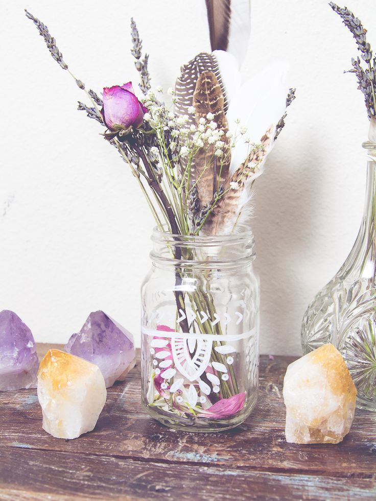 a glass jar with tribal patterns, dried and fresh blooms and feathers for a boho summer wedding