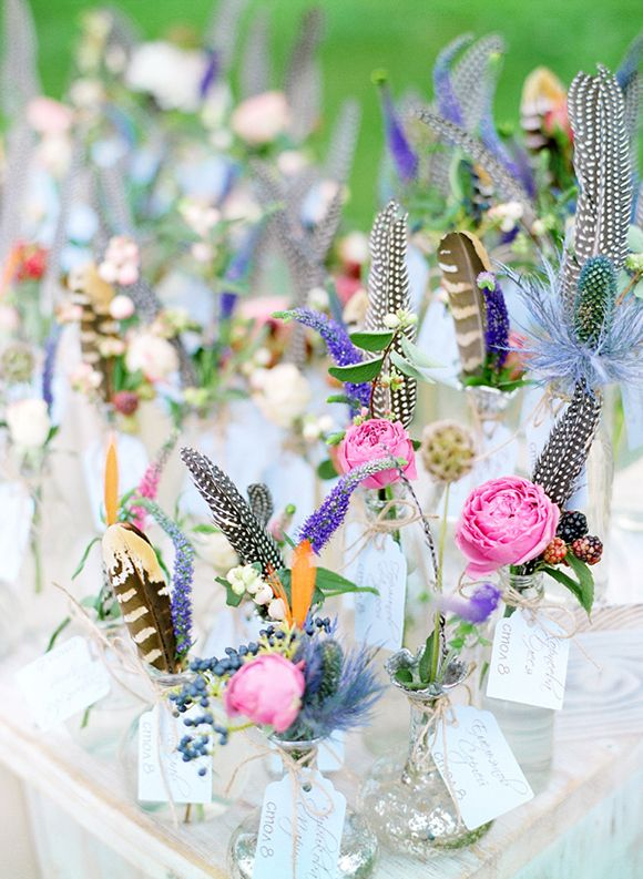 colorful blooms and feathers with table numbers in metallic vases for a summer boho wedding