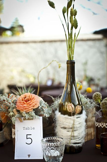 centerpieces of peachy blooms, pale greenery, a bottle with dried herbs and blooms