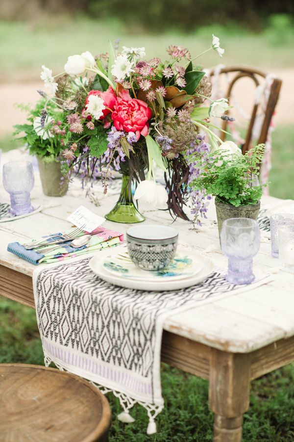 a bright and colorful floral wedding centerpiece with greenery in a green vase for a summer boho wedding