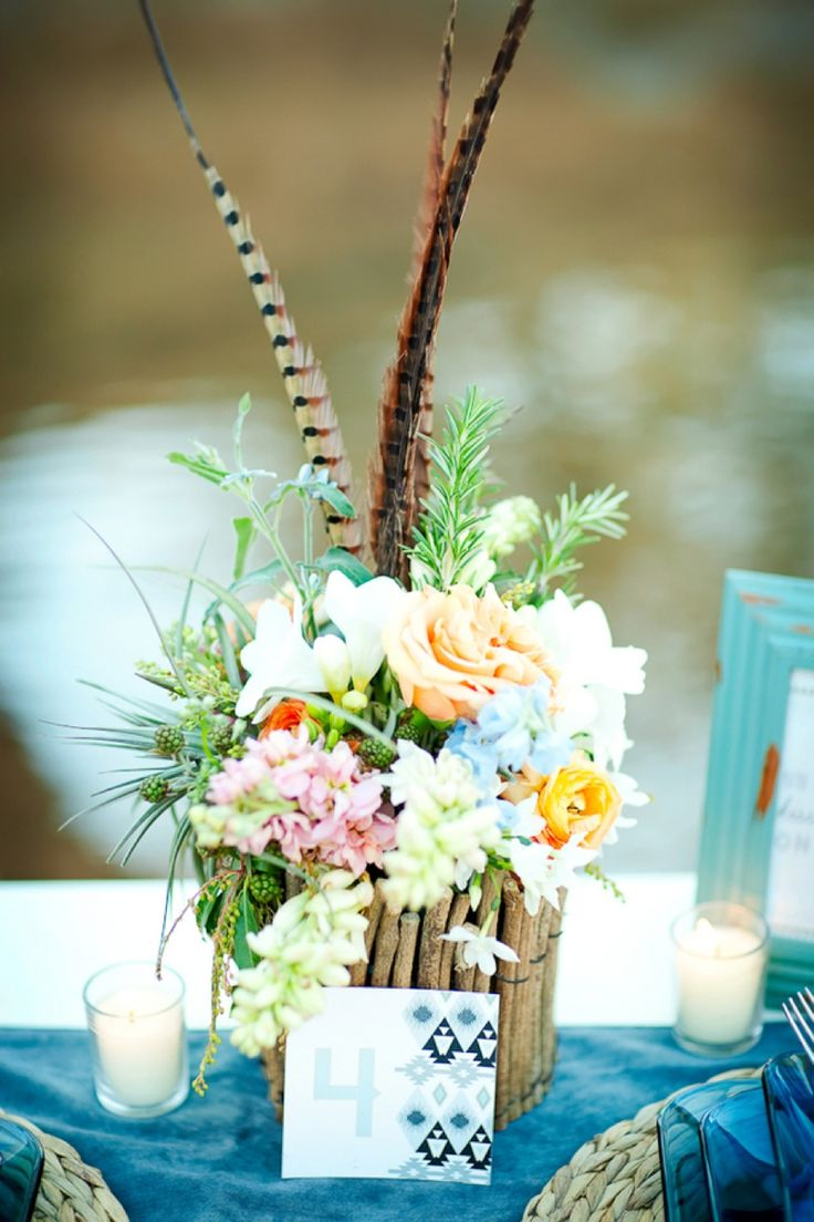 a colorful floral wedding centerpiece with greenery and feathers is amazing for a boho wedding