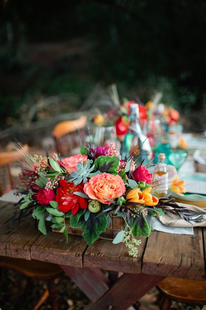 a lush and bright floral centerpiece with greenery and succulents plus mini apples looks boho and rustic