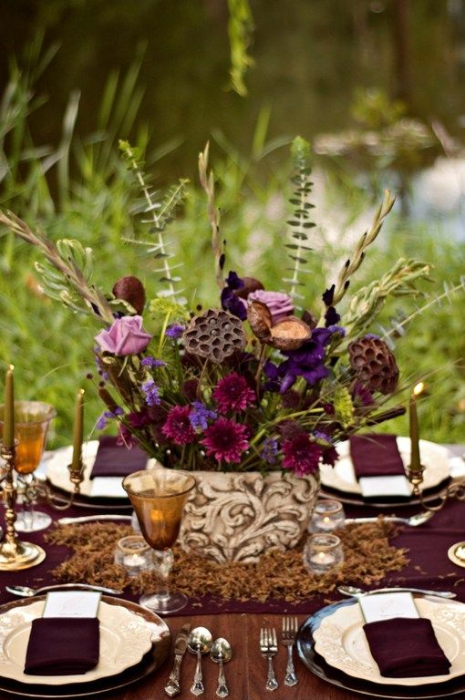 a refined and elegant dark bloom wedding centerpiece with lotus flowers, greenery and feathers for a moody boho wedding