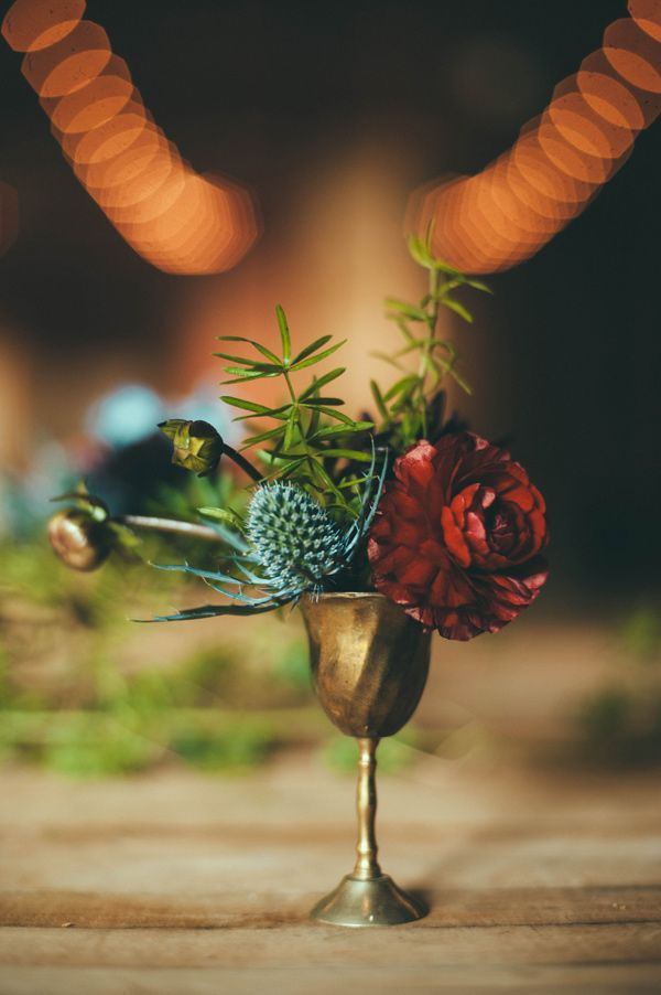 a gold goblet with bright blooms and thistles plus greenery for a vintage wedding with a boho feel