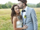 a grey suit and a black bow tie for a bold accent, a floral boutonniere and a brown hat create a chic and cool look