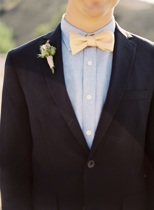 a black suit, a chambray shirt and a yellow bow tie plus a pastel floral boutonniere for a stylish look