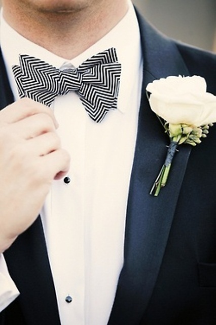 a black tux accented with a black and white geometric bow tie and neutral blooms for a refined and chic look