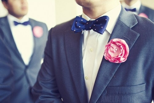 a grey suit with a navy polka dot bow tie and a pink bloom boutonniere is a chic option to rock on your big day