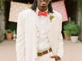 a white suit, a white shirt, a coral bow tie and a bright floral boutonniere for a cool spring or summer groom's look