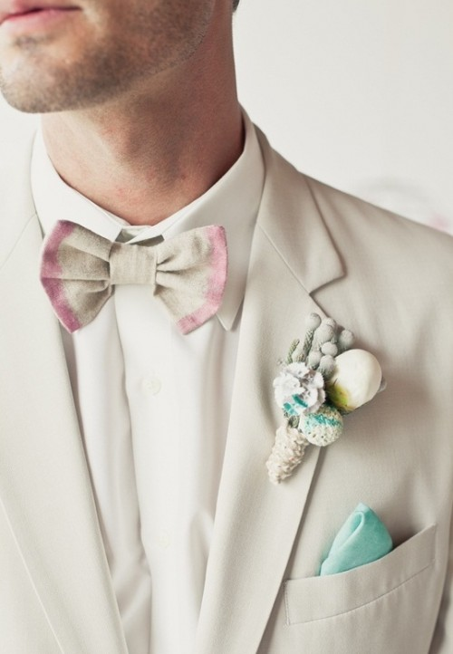 a neutral suit, a tie dye grey and pink bow tie and a snowy boutonniere for a chic and delicate groom's look