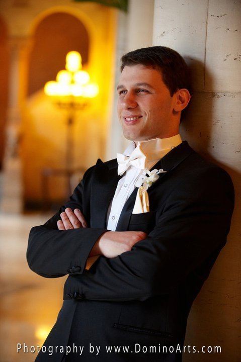 a black tux with a white bow tie and a white floral boutonniere for a stylish and elegant groom's look