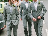 a grey suit, a grey shirt and a lemon yellow bow tie for a stylish summer groom's look