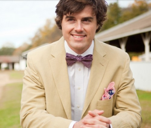 a tan suit, a white shirt, a pink printed bow tie and a colorful handkerchief for a stylish summer groom's look