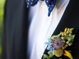 a black suit, a navy polka dot bow tie and a colorful floral boutonniere for a bold summer groom's look