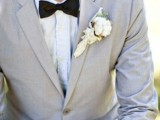 a light grey suit, a white shirt and a black bow tie plus a cotton boutonniere is an elegant and stylish groom's look