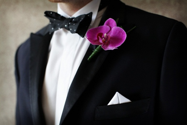 a black tux, a black and white polka dot bow tie and a pink orchid boutonniere for a luxurious and refined groom's outfit
