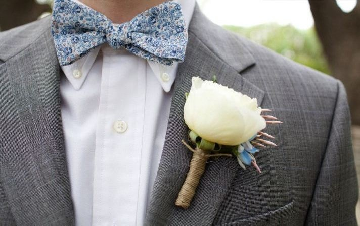 a grey suit, a white shirt and a blue printed bow tie and a white bloom boutonniere for an elegant and stylish spring groom's look