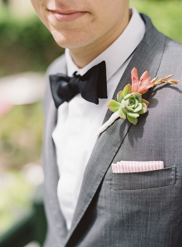 a grey suit, a white shirt, a black bow tie and a succulent boutonniere for an elegant spring or summer groom's look
