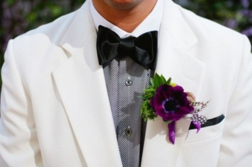 a white suit, a printed grey shirt, a black bow tie and a purple boutonniere that brings color to this monochrome