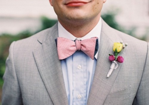 a light grey suit, a blue shirt, a pink bow tie and a colorful floral boutonniere for a bright summer look