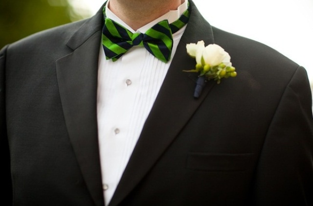 a cheerful green and black striped bow tie and a white bloom boutonniere make the outfit catchy and cool
