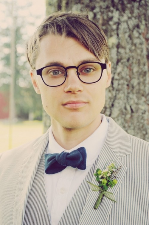 a striped grey and white suit, a navy velvet bow tie and a berry and bloom boutonniere for a spring or summer outfit