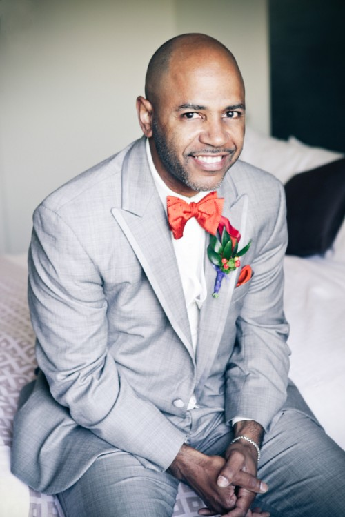 a dove grey suit, an orange bow tie and a matching floral boutonniere for a bold spring or summer look