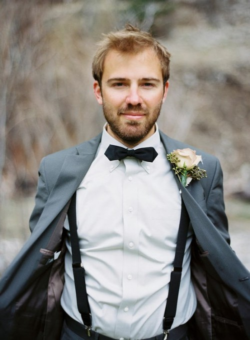 a grey suit, a black bow tie and suspenders plus a delicate floral boutonniere for a stylish summer or fall look