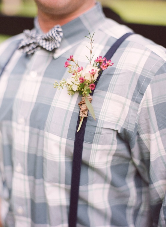 a rustic groom's look with a plaid shirt, a plaid bow tie, thin suspenders and a floral boutonniere