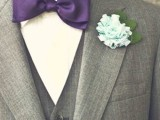 a conservative look with a grey three-piece suit, a purple bow tie and fabric flower boutonniere