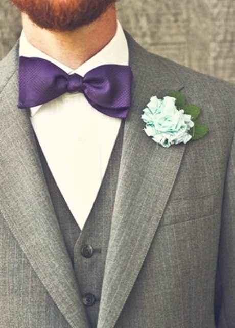 a conservative look with a grey three piece suit, a purple bow tie and fabric flower boutonniere