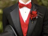 a black tux, a red waistcoat, a red bow tie and a bold floral boutonniere for a refined and vintage-inspired groom's look
