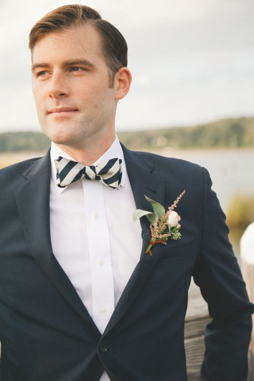 a black suit, a white shirt, a striped bow tie and a neutral floral boutonniere for a super elegant outfit