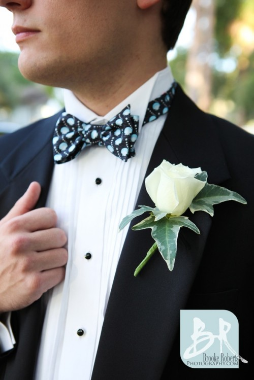 a black tux, a white shirt with black buttons, a black and blue printed bow tie and a white rose boutonniere for pure elegance