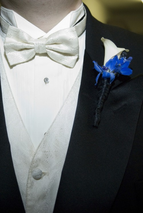 a morning suit with a white waistcoat and a matching bow tie and a white and blue floral boutonniere for an elegant touch