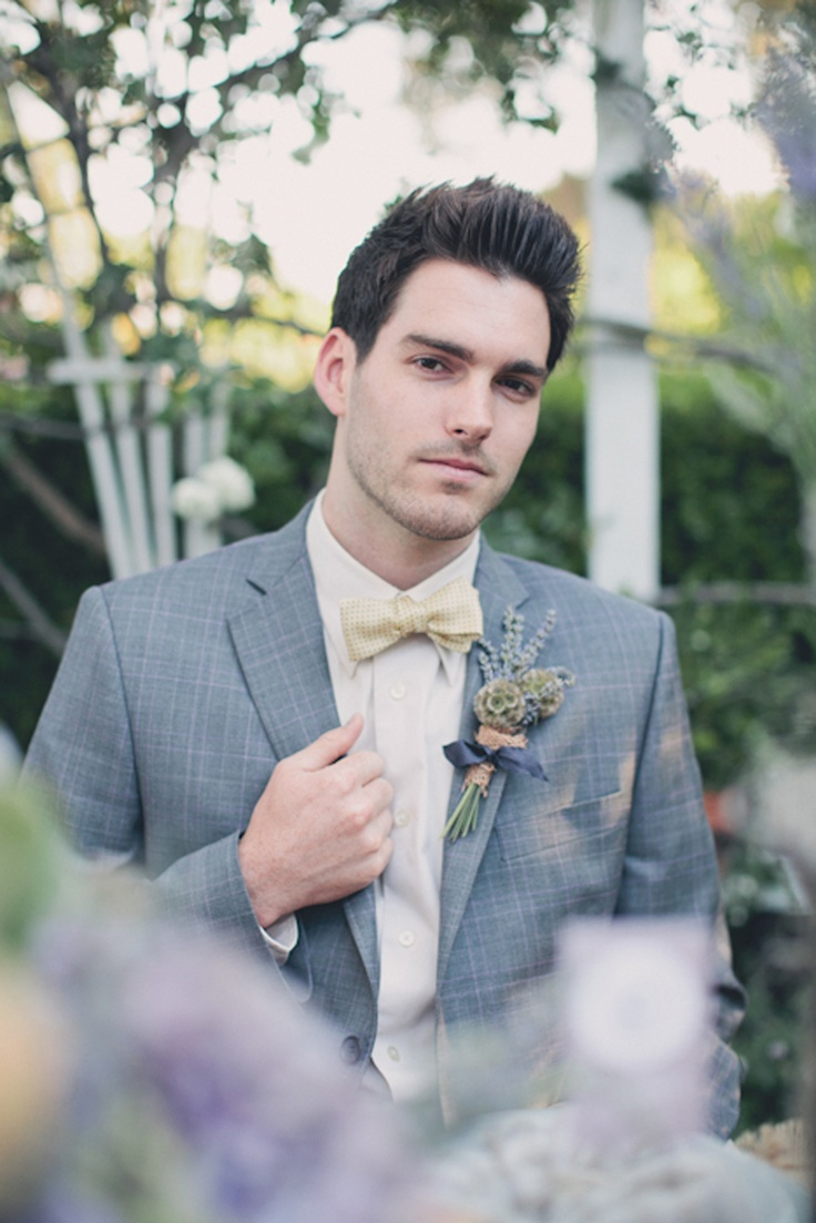 a plaid grey suit, an ivory shirt and a plaid yellow bow tie plus a floral boutonniere