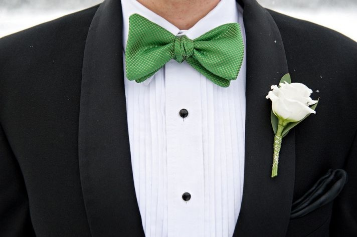 a black tux, a white shirt with black buttons, an apple green bow tie and a neutral floral boutonniere for an elegant and refined look