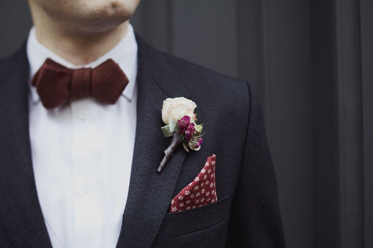a black suit, a chocolate bow tie, a white floral boutonniere and a printed handkerchief for a refined and chic look in the fall or winter