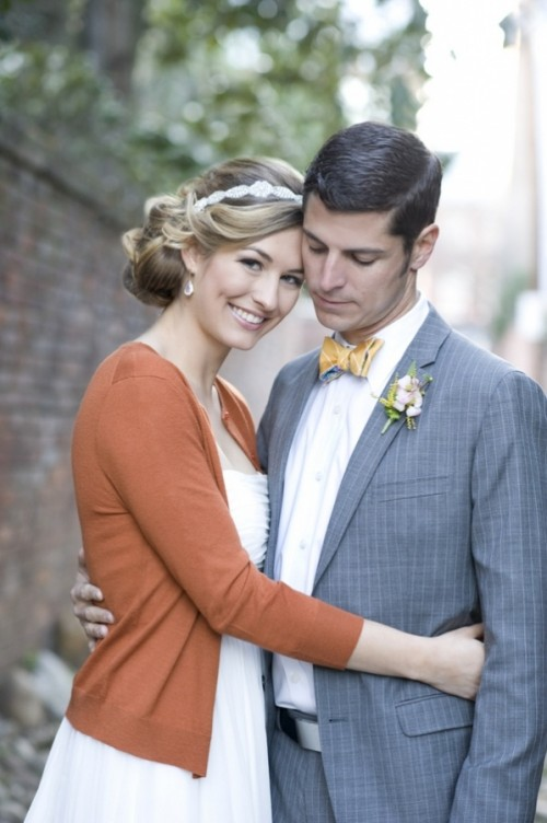 a striped gold bow tie and a pastel floral boutonniere accent the grey suit and add chic to it