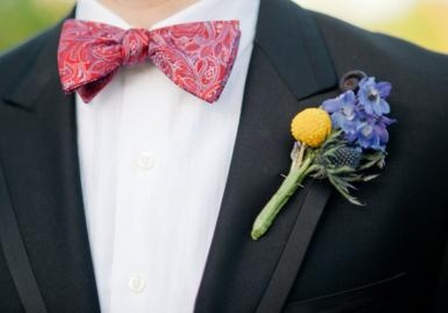 a black tux, a printed pink bow tie, a colorful floral boutonniere that refreshes and accents the look
