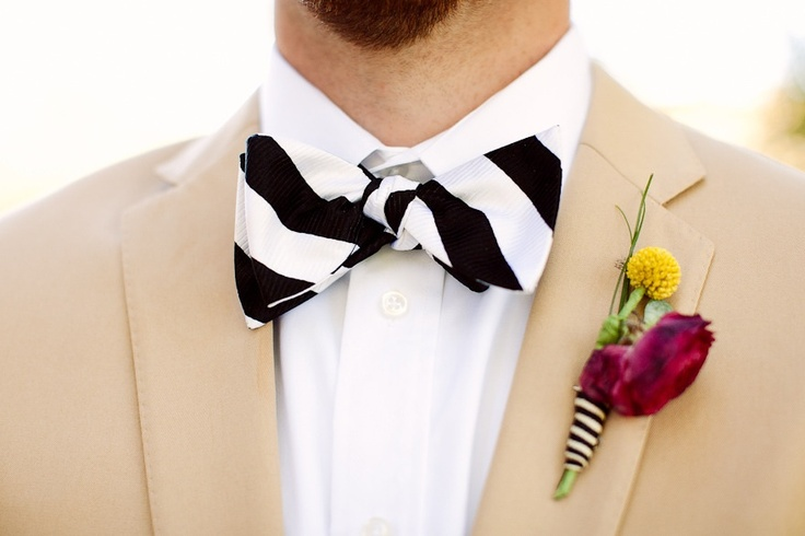 a tan suit, a striped bow tie, a colorful floral boutonniere for a bold and cool summer groom's look