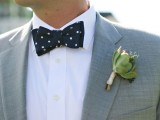 a grey suit, a navy polka dot bow tie and a succulent boutonniere for an elegant and modern look