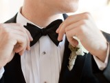 a black bow tie with a black tux are classics for an elegant formal wedding, add a white floral boutonniere for more chic