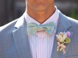 a grey suit highlighted with a pink and white striped shirt and a printed colored bow tie plus a floral boutonniere